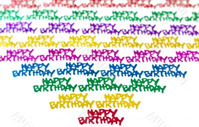 Colourful background of multicolored happy birthday confetti pieces