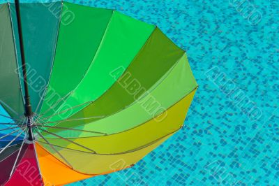 Colorful umbrella on a swimmingpool water  background