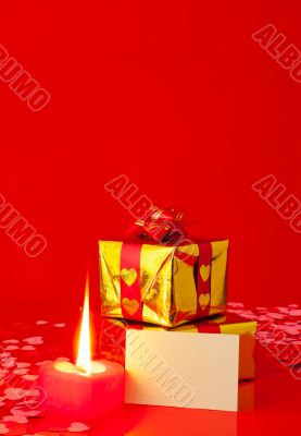 Presents and burning heart shaped candle with blank card