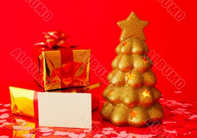 Two presents, blank card and golden evergreen tree