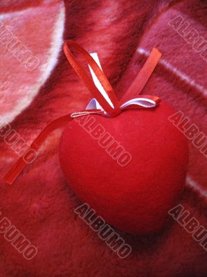 Red heart with red and white stripes on the pink background