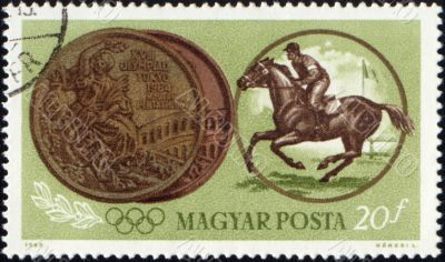 Sportsman riding horse and Olympic medal on post stamp