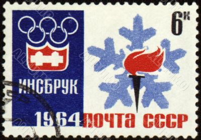 Olympic torch and emblem on post stamp