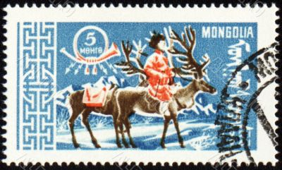 Man with reindeer in winter time on post stamp