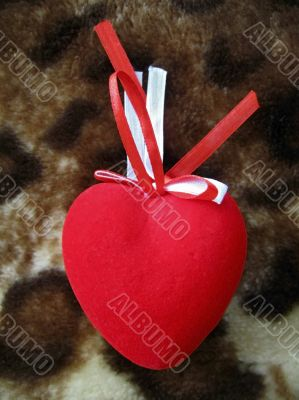 Red heart with red and white stripes on the brown background