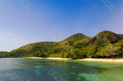A small turquoise crystal clear tropical beach by hill