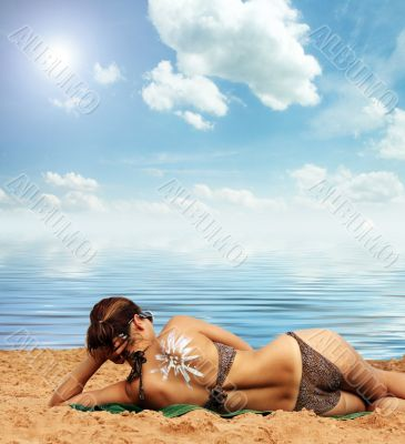 on the beach with suntan lotion on her back