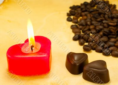 Burning candle, two heart shaped candies and cofee beans