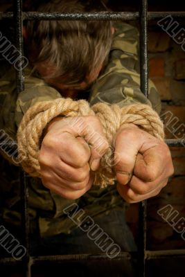 Man with hands tied with rope
