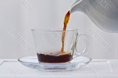 Pouring coffee into a quarter full cup