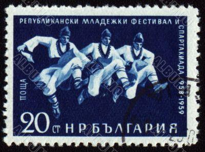 Three dancing men in Bulgarian national costumes on post stamp