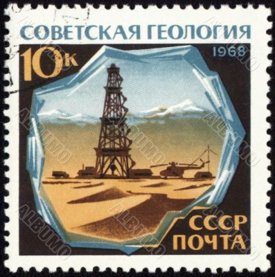 Drilling rig in desert on post stamp