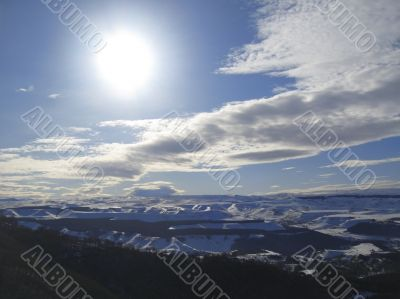 Caucasus mountains under big sun and clouds