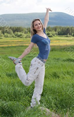 Beautiful girl stand on one leg in green field