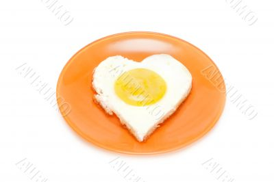 Fried egg in form heart on plate