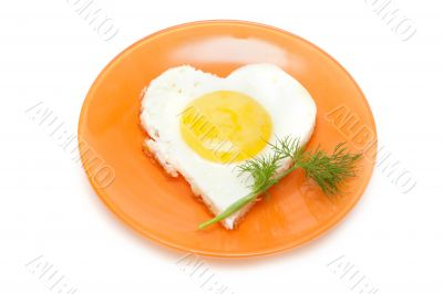 Fried egg in form heart on plate with dill