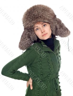 Beautiful girl in green sweater and fur hat