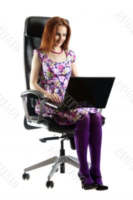 Beautiful girl in easy chair with computer