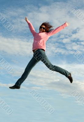 Girl in jump on background sky