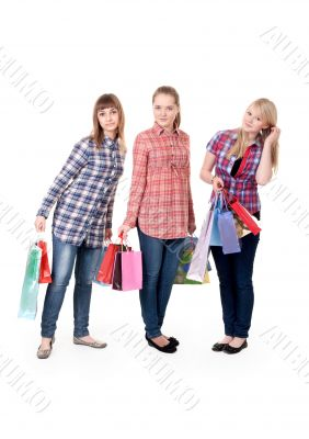 Three girls with colorful shopping bags