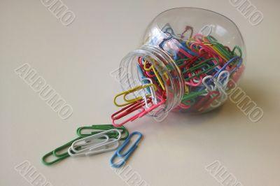 spilled colored paper clips jar