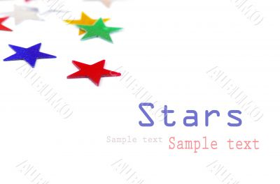 Christmas decoration of colored confetti stars against white bac