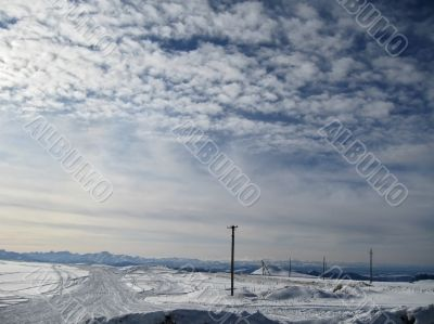 Blue sky with a little clouds and winter caucasus mountain lands