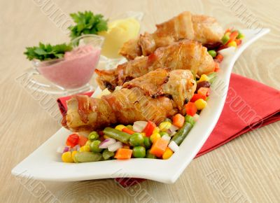 Roast chicken leg wrapped in bacon with vegetables