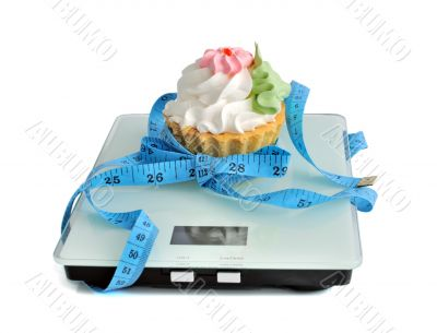 Cake on the scales measuring tape wrapped