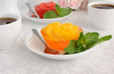 A cup of coffee and orange jelly with slices of fresh orange
