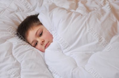 The boy lies in bed covered with a blanket