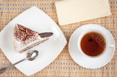 Tea and a slice of cake with cream