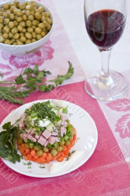 A delicious salad with mayonnaise and a glass of red wine