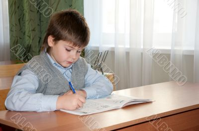 Schoolboy at his desk in the classroom makes the lessons