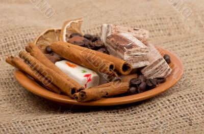 Sweets, cinnamon, nuts and coffee beans on a saucer, on burlap b