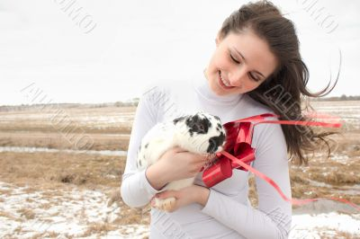 A woman holds a rabbit in her arms and smiles