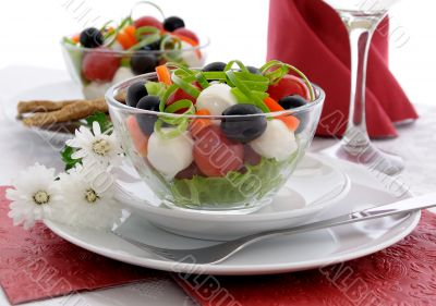 Salad of lettuce, cherry tomatoes, olives and mozzarella with pe