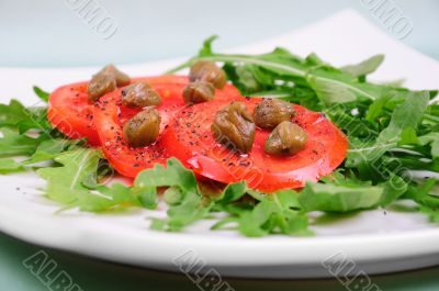 Salad with fresh tomatoes, capers and arugula