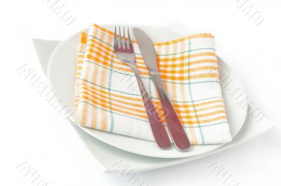 Napkin, folded on a plate with knife and fork
