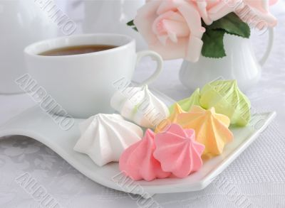 A cup of coffee and biscuits meringue on a plate