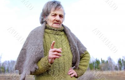 The old grandmother is facing and finger