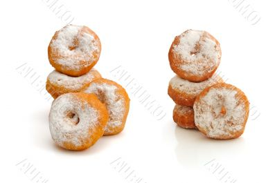 Fried donuts in powdered sugar on a white background