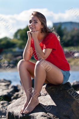 girl in a red sweater sits on a rock