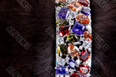 bracelet with precious stones in a dark fur
