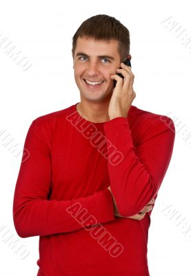 man in a red dress speaks on a mobile phone.