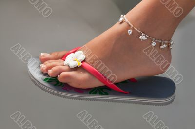 Women`s leg with a bracelet in thong