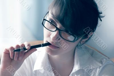 A woman holds a pen in his mouth and listen