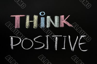 Think positive - text written with chalk on blackboard