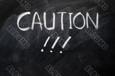 Caution written on blackboard