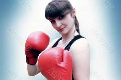 A woman stands in the boxer's gloves